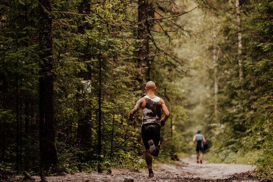 muddy runner athlete running forest autumn trail
