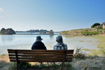Un couple assis sur un banc face au moulin à marée du Birlot sur l'île de Bréhat en Bretagne. France
