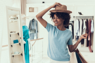 Smiling Young Woman trying on New Hat in Store