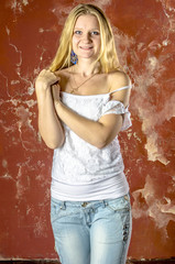 Young blond girl in jeans and a white sweater