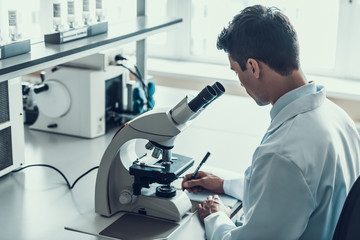 Young Scientist using Microscope in Laboratory