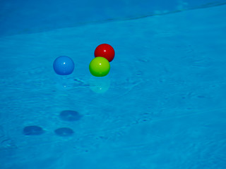 Multicolored balls on the surface of the blue pool.