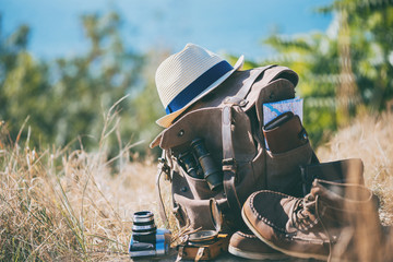 Looking image of travelling concept, essential vacation items. Background of nature. Close-up.