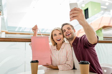 young man taking selfie with girlfriend showing shopping bag at table with disposable cups of coffee in cafe