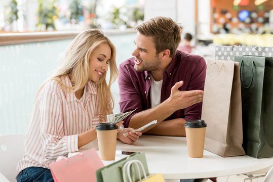 smiling young woman counting cash money after shopping while her upset boyfriend sitting near at table with coffee cups and paper bags in cae