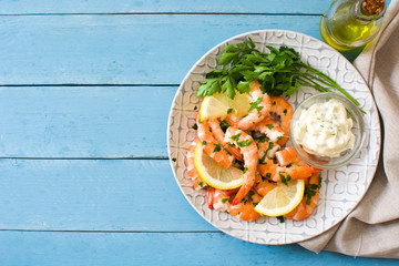 Grilled shrimps, parsley and lemon on blue wooden table. Top view. Copyspace