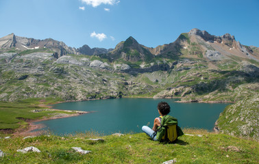 woman hiker looking at Lake Estaens in the Pyrenees mountains