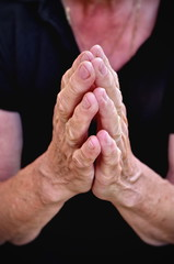 Elderly woman praying,wrinkly hands of elderly woman praying, religion concept
