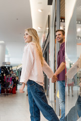 low angle view of smiling couple walking out from store at shopping mall