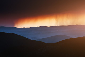 Rain in mountain landscape with clouds at sunset