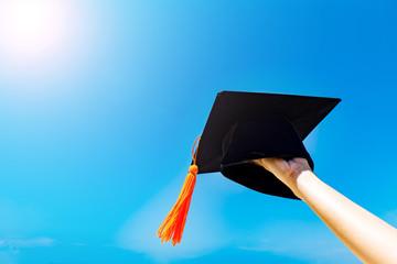 Graduate celebrating put graduation cap up to the sky,Education Success in summer Concept
