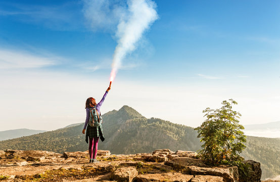 A woman in the wild mountains gives a distress signal SOS using Falsch feuer torch from which comes a bright flame and orange smoke, Concept of emergency situation during hike in the woods