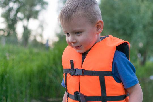 A little boy in a life jacket in a boat.
