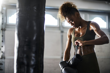 african american woman covered in sweat from boxing punching bag taking off gloves