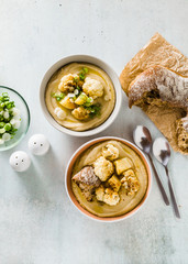 cream soup of cauliflower and potatoes in bowls on a table with fresh bread and green onions. healthy vegan cuisine.