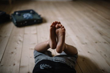 Pieds d'enfant avec cartable sur le sol