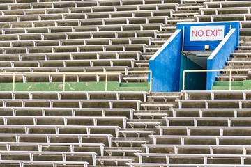Empty bleachers section at an outdoor stadium with No Exit signage.