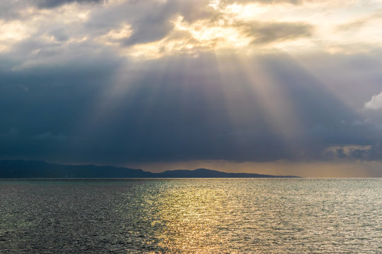 Scenic view of sun rays bursting through clouds over the ocean. Concept of breakthrough, hope, signs.