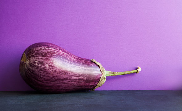 Ripe purple eggplant on violet black background. Organic vegetable with beautiful striped pattern. Copy space