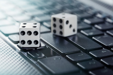 Dice on laptop computer keyboard. Сoncept of online gambling and online casino. Creative idea with devil's bones and PC keyboard.
