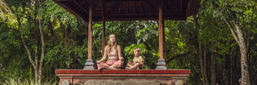 Mom and son meditate practicing yoga in the traditional balinesse gazebo BANNER, long format
