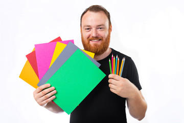 Adult bearded man holding heap of multicolored paper sheets isolated on white background and smiling away