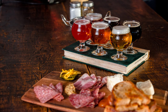 A Flight Of Beer With A Plate Of Pub Food