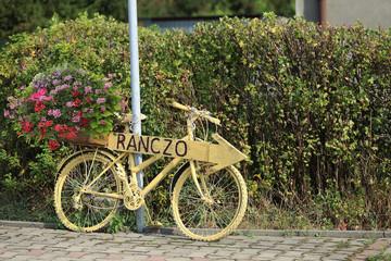 Rower z kwietnikiem, różowe i czerwone kwiaty, dekoracja dom i ogród.