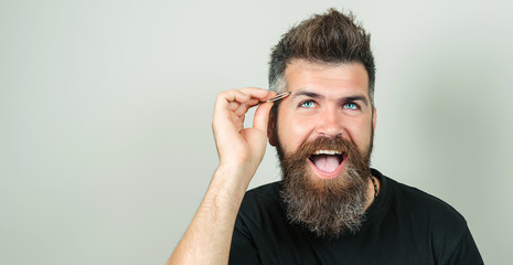 Eyebrow Correction. Closeup Of Beautiful Funny Man Plucking Eyebrows. Portrait Of Sexy Male With Beard Model Face And Tweezers Near Brows. Beauty Concept. High Resolution