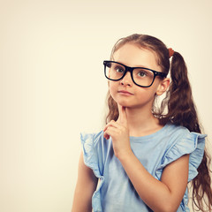 Fun grimacing happy girl in eye glasses thinking and looking up on background with empty copy spase. Toned closeup vintage portrait