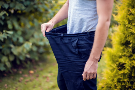 Young man wearing big loose jeans - weight loss concept