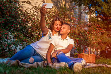 Woman with her teenager son taking selfie on smartphone. Happy family spending time outdoors sittting on grass in park.