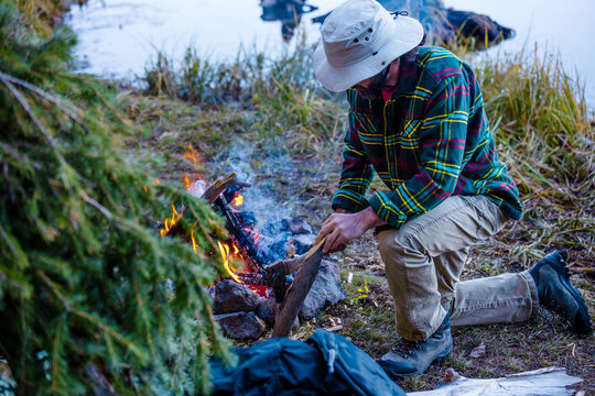 A Male Outdoorsman Building A Campfire At His Remote Shelter