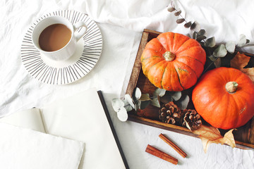 Autumn breakfast in bed composition. Blank card, notebook mockup. Cup of coffee., eucalyptus leaves and pumpkins on wooden tray. White linen bed sheet background. Thanksgiving, halloween concept. Flat