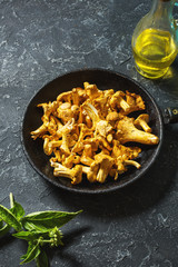 Fresh chanterelle mushrooms in a pan on a black table