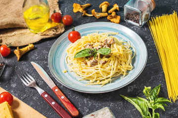 Pasta with chanterelle mushroom and ingredients on a dark stone background