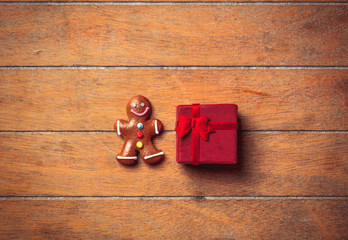 gingerbread man with Christmas gift on wooden table. Above view in old color style