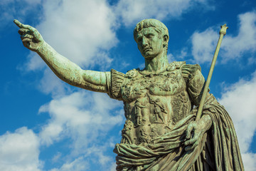 Fototapeta Caesar Augustus, the first emperor of Ancient Rome. Bronze monumental statue in the center of Rome, with clouds obraz