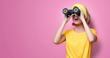 Young redhead girl in yellow t-shirt and blue jeans holding binoculars on pink background
