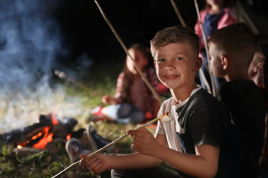 Little boy with marshmallow near bonfire at night. Summer camp