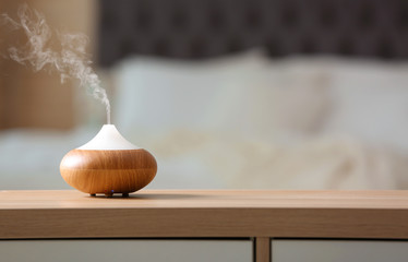 Aroma oil diffuser lamp on cabinet against blurred background