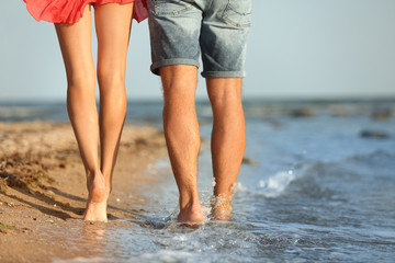 Young couple spending time together on beach, closeup of legs