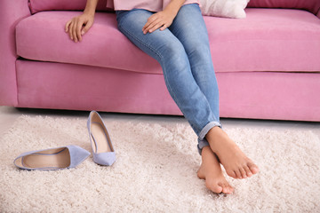 Barefoot woman with tired legs sitting on sofa at home, closeup view
