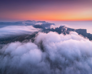 Wall Mural - Aerial view of low clouds, mountains, sea and colorful sky at sunset. Above the clouds at dusk. Seashore in Spain. Top view from drone. Amazing landscape with cloudy sky and rocks. Nature background