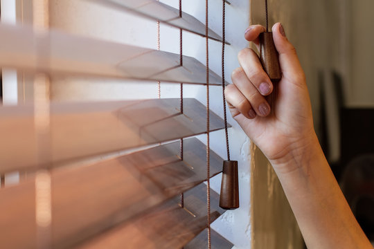 The woman's right hand holds one of the control strings of the wooden shutters on the window.