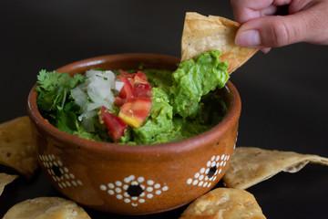 Guacamole mexicano tradicional de la salsa en el cuenco de arcilla y nachos en el fondo de un tablero de pizarra