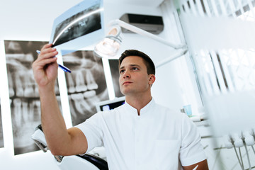 Handsome and attractive male dentist looking at dental x-ray.