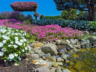 waterfall in colorful summer rock garden with bright blue sky