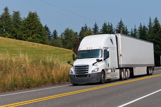 Big rig white semi truck with dry van semi trailer transporting goods on the road with forest and meadow