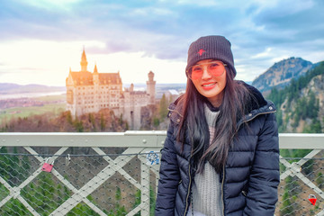 Young woman tourists at Queen Mary's Bridge with the view of Neuschwanstein Castle in late winter, Bavaria, Germany.